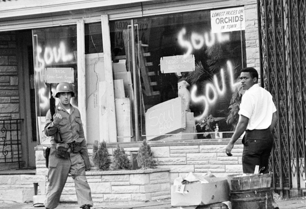A National Guard officer passes the smashed window of a black-owned flower shop in riot-torn Newark, N.J., in this July 15, 1967, file photo. Dozens of shops and stores had been stripped clean in three days of racial rioting. The 40th anniversary of the riots that devastated Newark has rekindled a sometimes acrimonious debate on the causes and effects of the events of July 1967 that sent the city on a downward spiral from which it took decades to recover. (AP Photo)